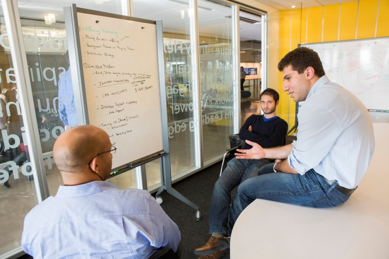 Three VDC coworkers gather around a whiteboard to discuss business strategy.